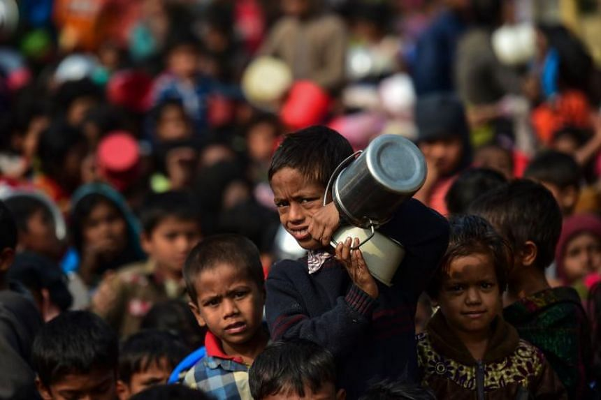 A Rohingya Muslim refugee waits with others for food aid at Thankhali refugee camp in Bangladesh's Ukhia district on Jan 12, 2018.