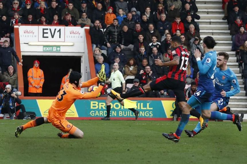 Bournemouth's English striker Callum Wilson (centre) scores his team's first goal past Arsenal's Czech goalkeeper Petr Cech during the English Premier League football match between Bournemouth and Arsenal at the Vitality Stadium in Bournemouth, south