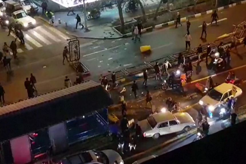 A screengrab from a video reportedly shows a group of men pushing traffic barriers in a street in Tehran on Dec 30, 2017.