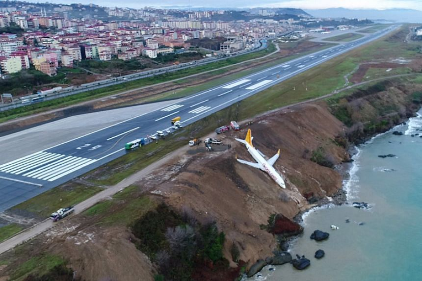 Dramatic images showed the Pegasus Airlines plane dangerously hanging off a cliff several metres from the Black Sea, its wheels stuck in mud.