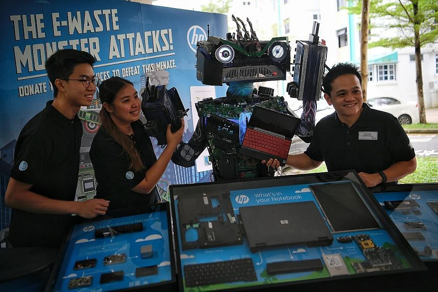 (From left) HP Singapore intern Darren Chia, marketing manager Sheryl Chan and managing director Lionel Chng with the E-waste Monster at the HP Make IT Green Campaign, held in conjunction with South West Community Development Council's annual trash-f