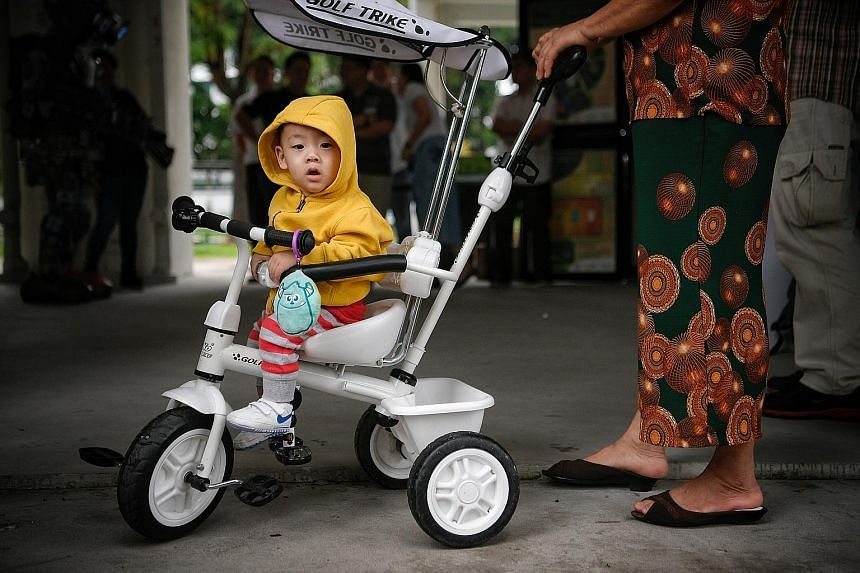 A little boy warmly dressed while taking a ride in Bukit Batok Street 51 yesterday. The thermometer reading dipped to 21.2 deg C in Admiralty and Jurong West at around 5am yesterday morning.