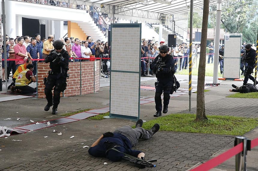 """Police officers responding to a simulated attack by """"gunmen"""" near Taman Jurong Community Club yesterday. The live exercise was part of the Taman Jurong Emergency Preparedness Day - an event held in constituencies islandwide under the SGSecure program"""