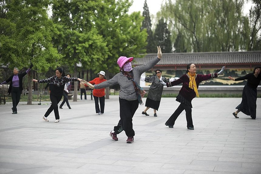 """Women going through their square dancing routine at a park in Beijing. The activity is now so popular that it has even been considered a sport, and its participants, mostly middle-aged and elderly Chinese women, have been described as """"walking wallet"""