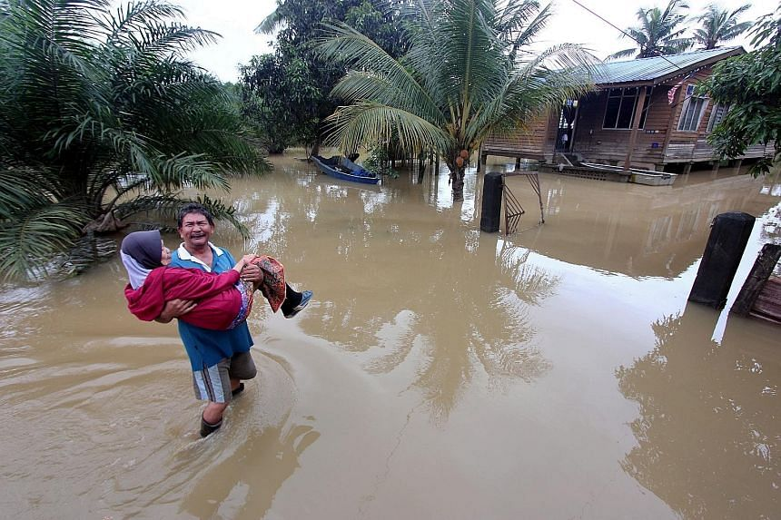 Mr Azhar Osman, 56, carrying his 75-year-old mother Rabayah Abdul Hamid to safety after floodwaters inundated his house compound at Kampung Gudang Rasau yesterday. The flood situation in the state of Pahang eased slightly with the number of evacuees