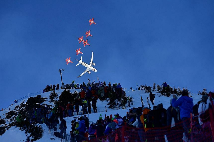 Fighter jets of the Patrouille Suisse, the aerobatic team of the Swiss Air Force, and a commercial plane flying over the ski slopes of Wengen, Switzerland, in an aerial display ahead of the men's downhill race at the FIS Alpine Skiing World Cup last