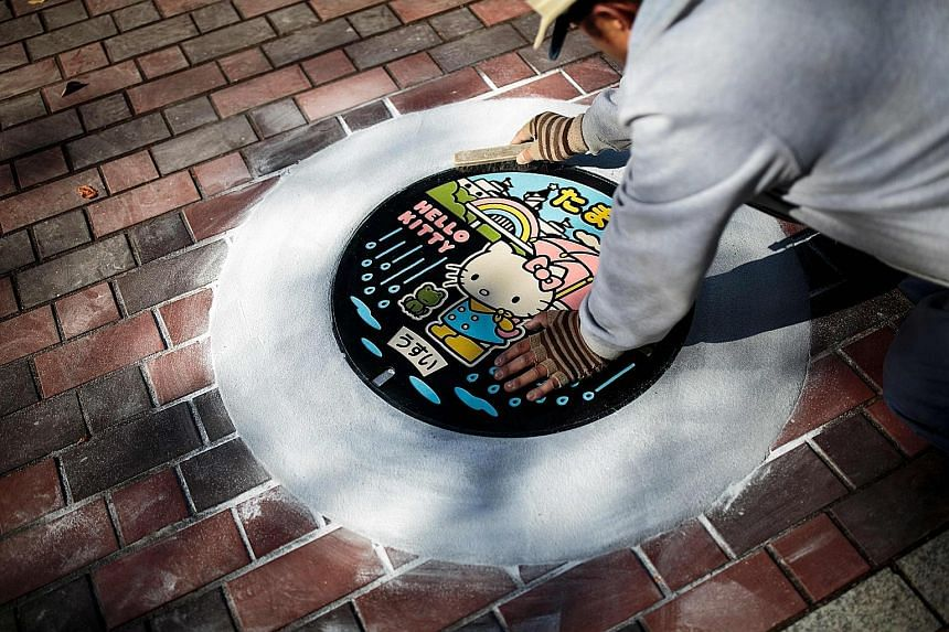 Above: Specially designed manhole covers in Kawaguchi in Japan's Saitama prefecture. Left: Hello Kitty adorns a manhole cover in Tama, which has a theme park featuring the much-loved Sanrio character.