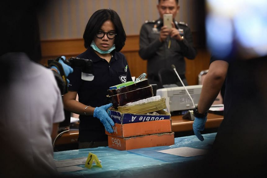 "An employee from Thailand's Department of Special Investigation sorts through evidence from the ""Victoria Secret"" massage parlour in Bangkok on Jan 15. Police had raided the premises on Jan 12 due to suspicions of underage trafficking and prostitutio"