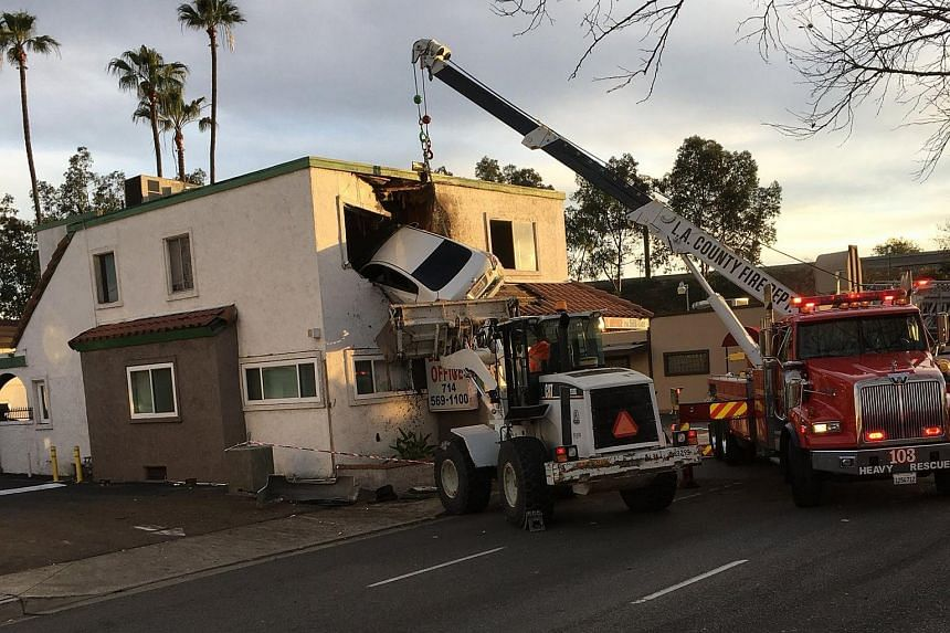 Workers with heavy equipment removing a Nissan Altima from the second story of a dental office building in Santa Ana, California, on Jan 14, 2018.