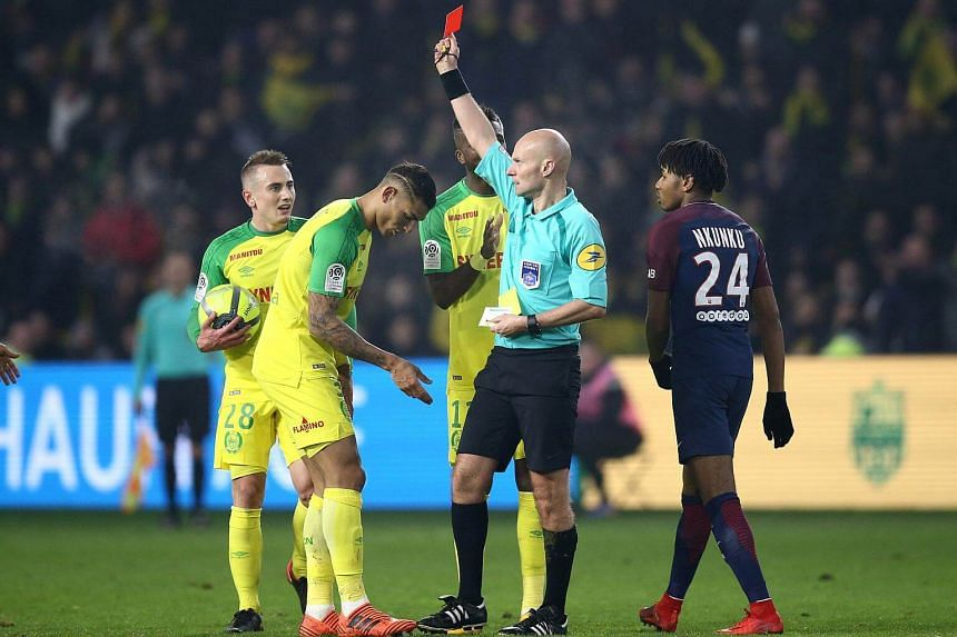 Referee Tony Chapron showing Nantes' Diego Carlos the red card after kicking out at him following a tumble.