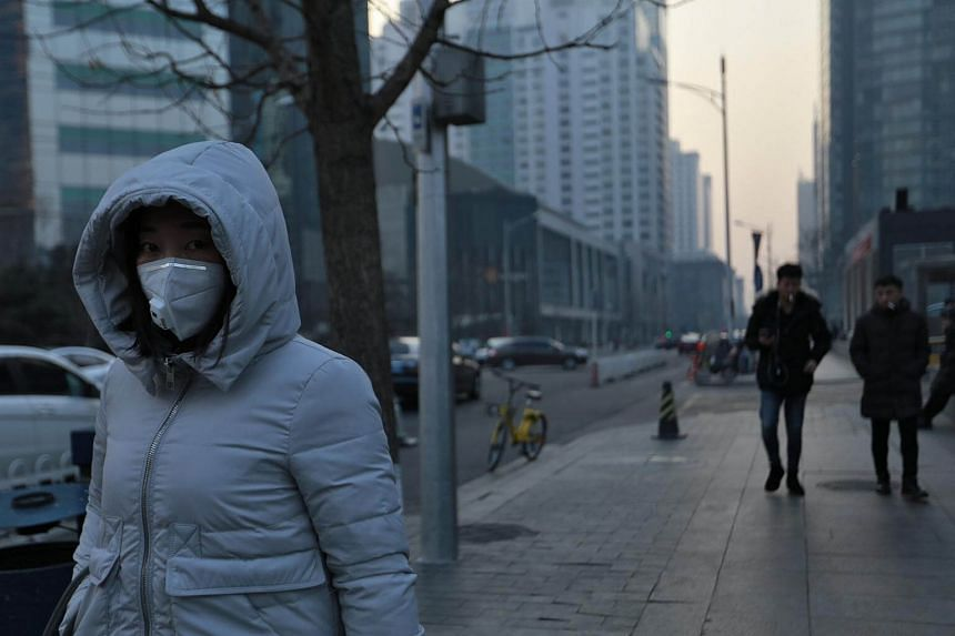 A woman wearing a mask walks by as smog shrouds buildings in Beijing, on Jan 13, 2018.