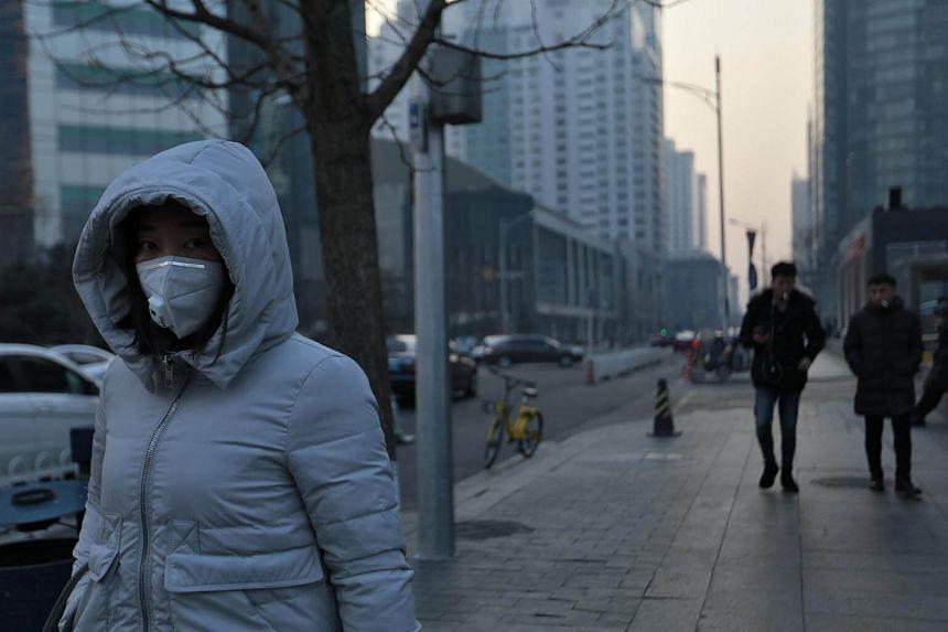 A woman wearing a mask walks by as smog shrouds buildings in Beijing, on Jan 13, 2018.