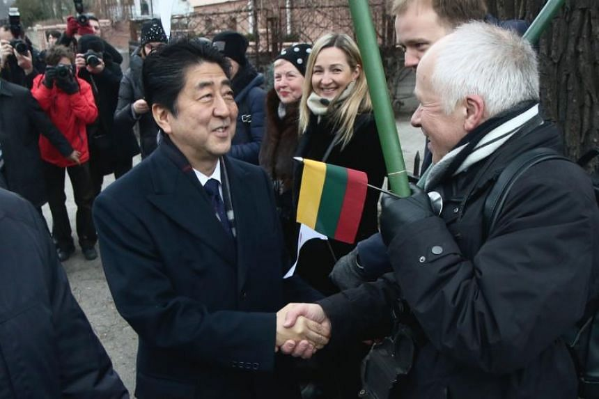 Japan's Prime Minister Shinzo Abe is greeted by local residents as he arrives at the Sugihara House in Kaunas, Lithuania, on Jan 14, 2018.