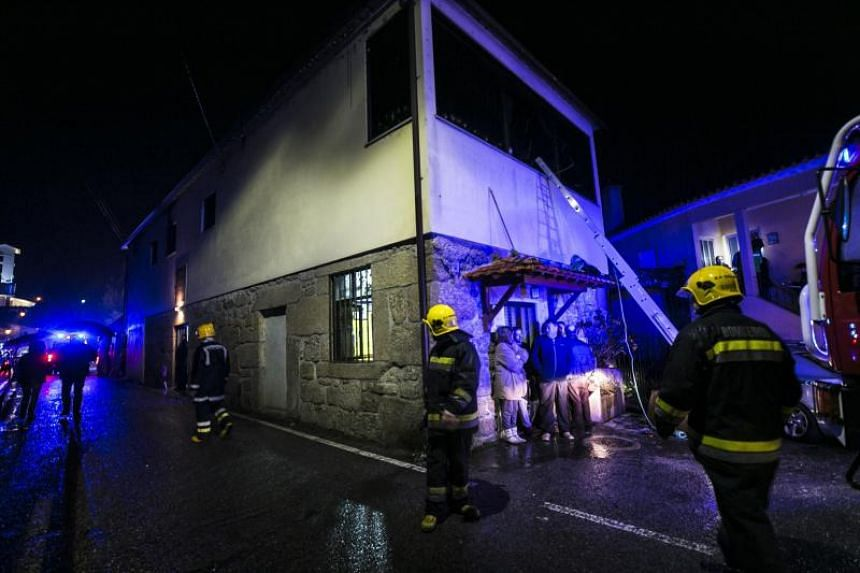 Firefighters stand outside the building of a local community centre where a fire killed eight people and injured 50 others in Vila Nova da Rainha in Tondela late on Jan 13, 2018.