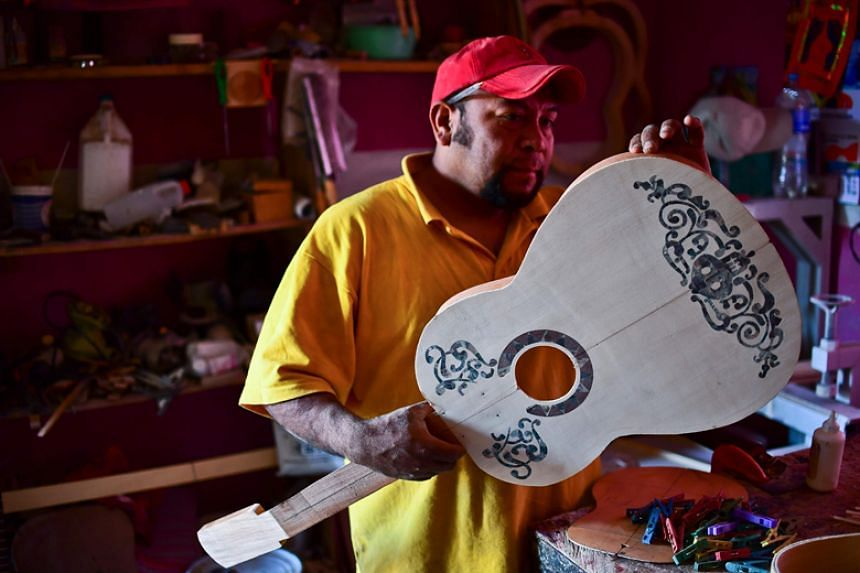 Mexican luthier Salvador Meza makes a replica guitar from the movie Coco at his workshop in Paracho on Jan 9.