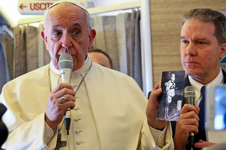 Pope Francis holds a picture depicting a Nagasaki victim as he speaks to reporters aboard the plane for his trip to Chile and Peru on Jan 15.