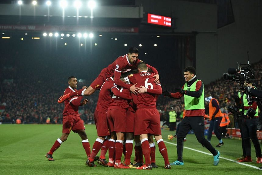 Liverpool's German midfielder Emre Can (centre) jumps into the celebration for the third Liverpool goal scored by Liverpool's Senegalese midfielder Sadio Mane.
