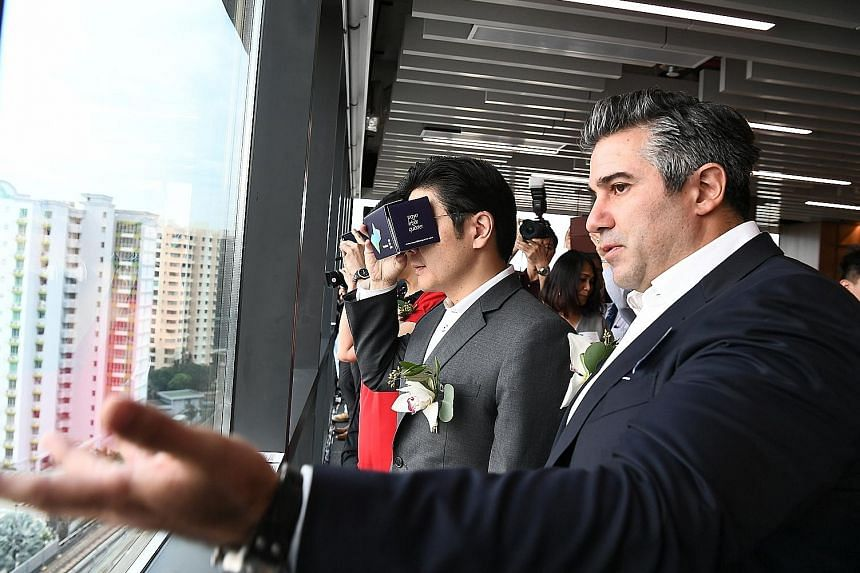 National Development Minister Lawrence Wong and Lendlease Asia chief executive Tony Lombardo at the topping-out ceremony of the first of Paya Lebar Quarter's office towers. Mr Wong is using a virtual reality headset that shows what the development wo