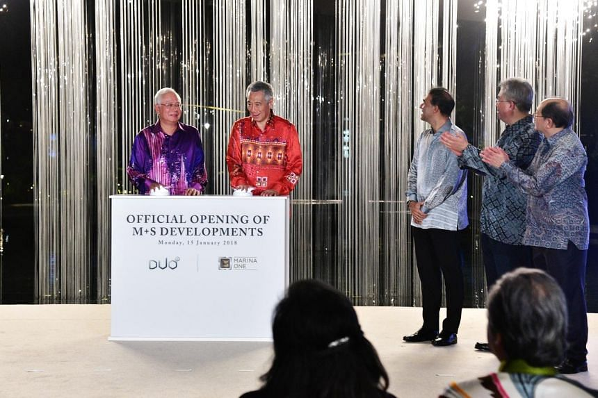 Prime Minister Lee Hsien Loong and his counterpart Datuk Seri Najib pressing the launch mechanisms to officially open Marina One and Duo at the ceremony last night. With them were (from right) Temasek International chief executive Lee Theng Kiat, Kha