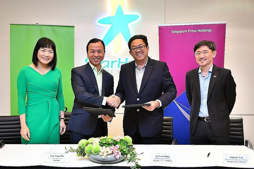 StarHub chief executive Tan Tong Hai (second from left) and SPH CEO Ng Yat Chung shaking on the agreement at the MOU signing yesterday, witnessed by StarHub chief strategic partnership officer Jeannie Ong and SPH deputy CEO Anthony Tan. The tie-up wi