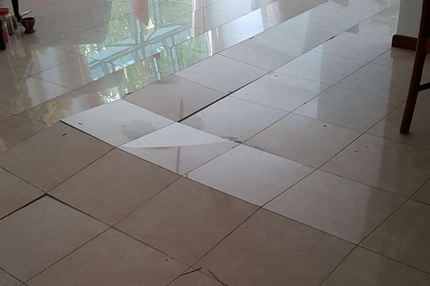 Half the tiles in Woodlands resident Lewis Sua's living room have popped and cracked. The tiles in his flat began popping on Jan 14, 2018.
