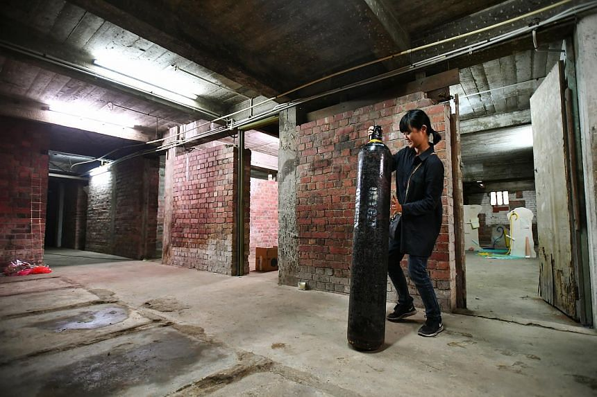 Artist Tay Ining, 29, setting up her work, inside the Tiong Bahru Air Raid Shelter.