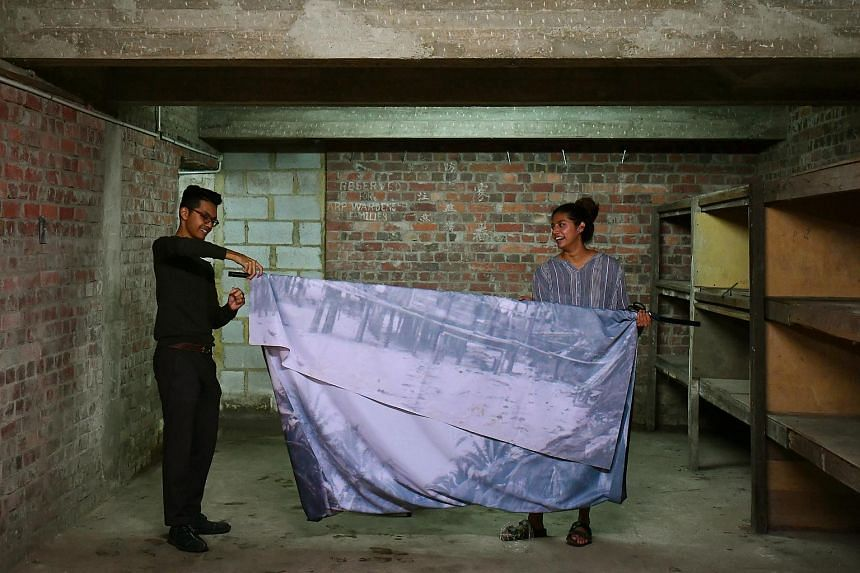 Mr Zulkhairi Zulkiflee, 27, setting up his work with help from Ms Pooja Kanade, 24, inside the Tiong Bahru Air Raid Shelter.