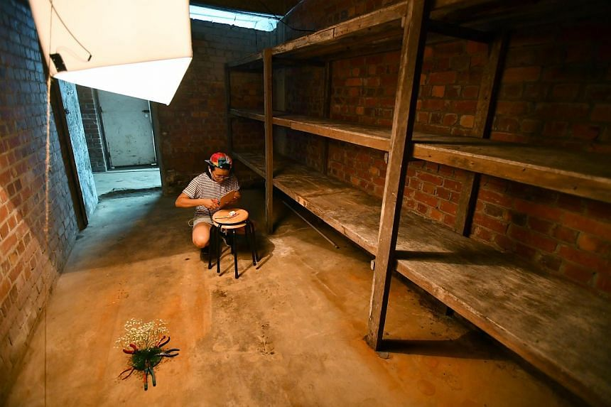 Ms Jacqueline Sim, 30, setting up her work titled, There Is A Time For Everything, And A Season For Every Activity Under The Heavens - A Time To Plant And A Time To Uproot, inside the Tiong Bahru Air Raid Shelter.