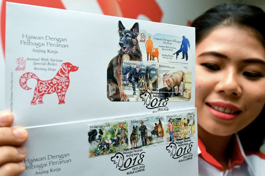"""Pos Malaysia Staff Nurul Nadia Natasha Zainal Abidin showing a stamp series with the issuance of an animal-themed series entitled """"Animal with Various Special Roles-Working Dogs"""" on Jan 16."""