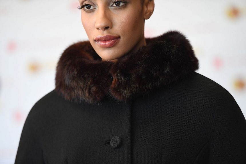 A model shows off a coat with a mink trim once owned by movie star Elizabeth Taylor, ahead of its auction.
