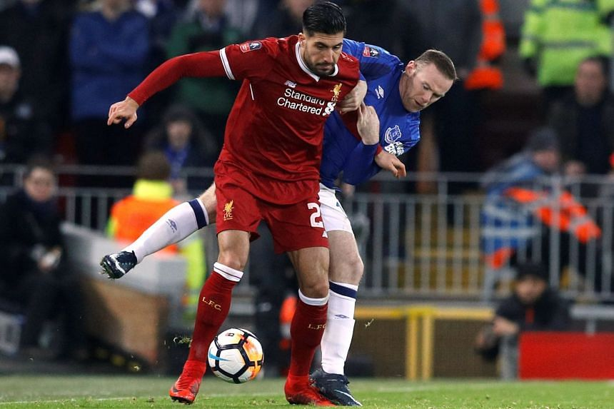 Liverpool midfielder Emre Can tussling for the ball with Everton's Wayne Rooney, during their FA Cup match on Jan 5, 2018.