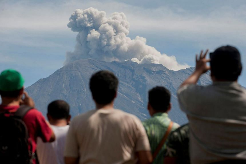 People watch from an obeservation post in Bali as Mount Agung spews ash and smoke during an eruption on Dec 9, 2017.