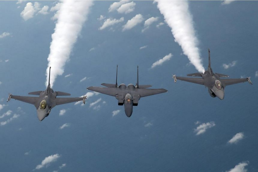 An F-15SG (centre) and two F-16s in formation in a training area north-east of Singapore, during a media preview to highlight the RSAF's 50th anniversary celebrations.
