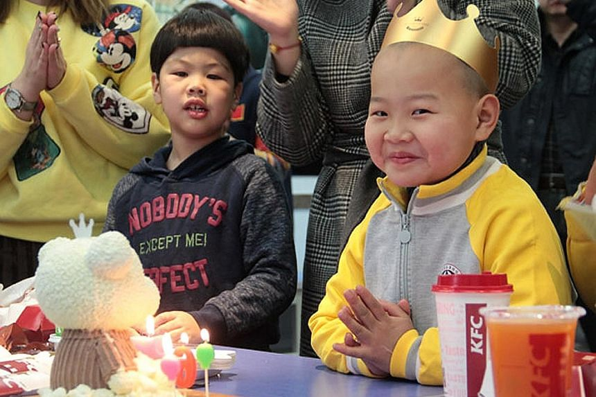 """The boy (right), nicknamed Xiaochangjiang, which means """"Little Yangtze River"""", celebrating his birthday for the first time on Sunday at a welfare home in Qingdao, Shandong province."""