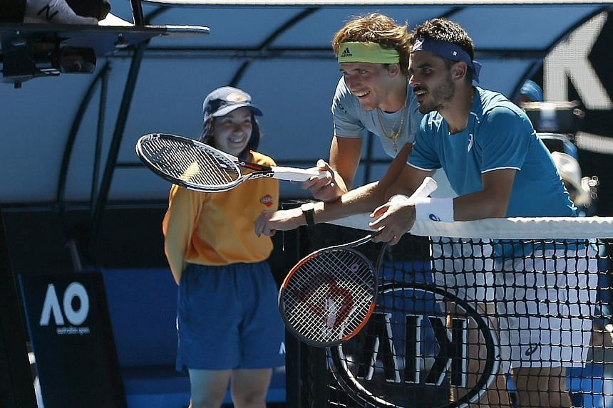Alexander Zverev and Thomas Fabbiano study a replay during the German's 6-1, 7-6 (7-5), 7-5 win yesterday. Zverev patted his opponent on the back before returning to his own side.