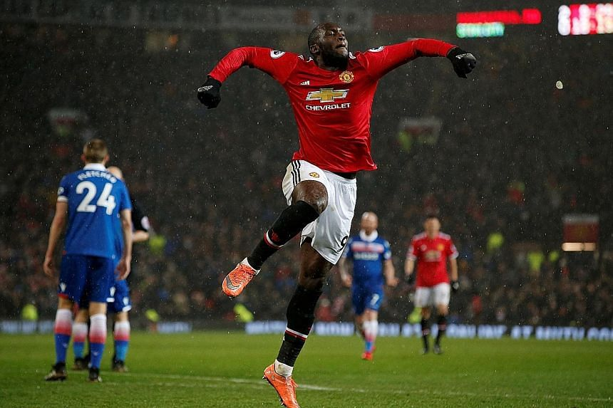 Manchester United striker Romelu Lukaku jumps for joy after scoring their final goal in Monday's 3-0 win against Stoke City that cut leaders Manchester City's lead to 12 points.