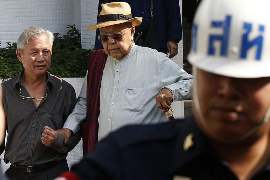 Thai author Sulak Sivaraksa (centre) leaves after a hearing on lese majeste indictment charges at the Martial Court in Bangkok, Thailand, on Jan 17, 2018.