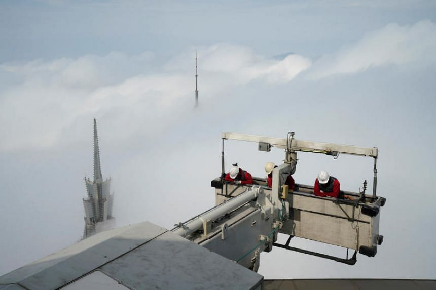 Workers clean the exterior of Shanghai World Financial Centre on a hazy day.