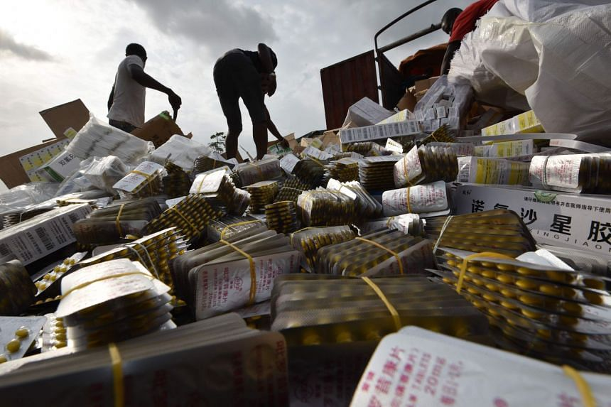 People unload boxes of counterfeit drugs from a truck at the cemetery of Abobo district, Abidjan, Africa, on March 10, 2017.