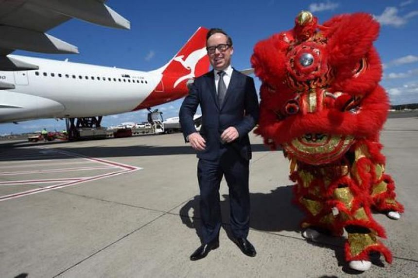 """Qantas chief executive Alan Joyce poses with an Airbus A330-200 aircraft and Chinese lion dance performers. The carrier said this week it had incorrectly listed on its website some Chinese territories as """"countries"""" and the company was fixing the err"""