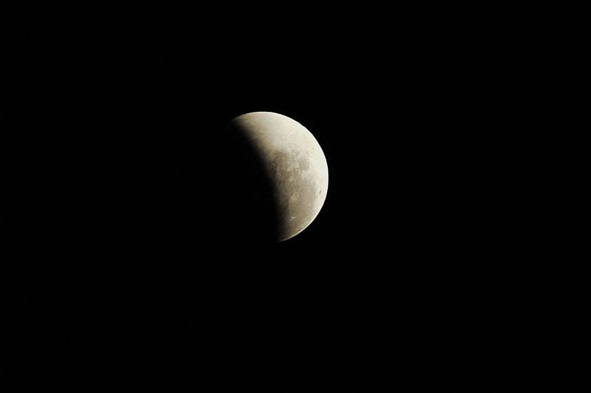 A photograph of the occurrence of a total lunar eclipse, shot at 11.45pm on Dec 10, 2011. On Jan 31, Singaporeans will get to see the rare coincidence of the blood moon, blue moon and supermoon phenomena - a total lunar eclipse, the second full moon