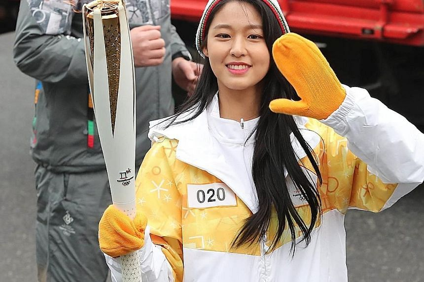 South Korean girl group AOA's Seol Hyun carrying the Winter Olympics torch in Seoul on Tuesday, as part of a nationwide relay tour.