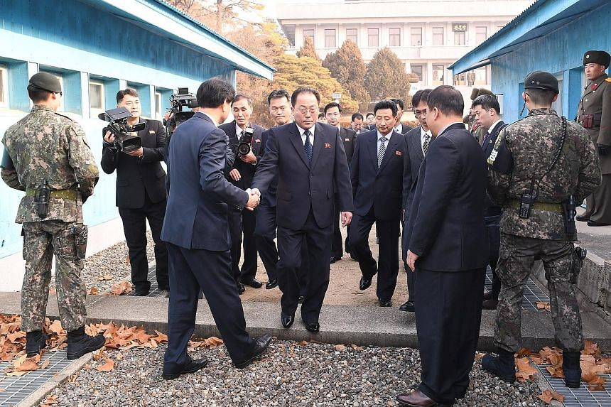 North Korean chief delegate Jon Jong Su (centre) and delegates heading to a meeting in the truce village of Panmunjom yesterday, as seen in this handout photo from the South Korean Unification Ministry. The two sides agreed to march together under a