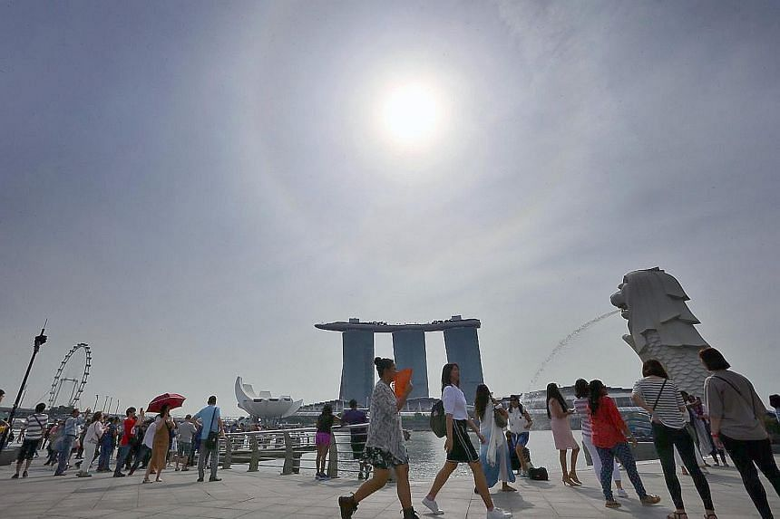 At Merlion Park on Tuesday. Fewer rainy days are expected in the second-half of the month, but rainfall for the month is expected to be well above normal, and daily temperatures will range between 24 deg C and 32 deg C.