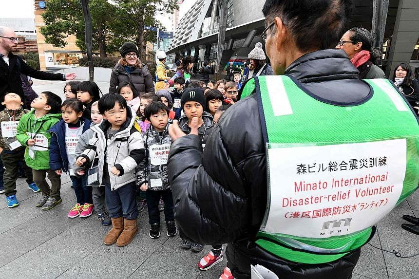Children from an international school listening to a volunteer interpreter during a disaster drill at the Roppongi Hills business and shopping compound in Tokyo yesterday, the 23rd anniversary of the Great Hanshin Earthquake that killed more than 6,4