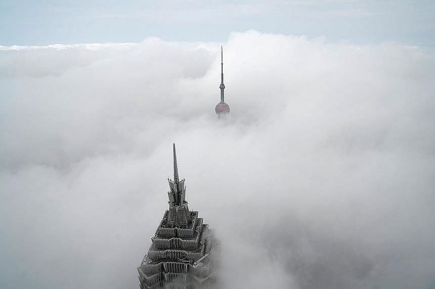 Shanghai's Oriental Pearl Tower is barely visible in the distance while only the top of the 88-storey Jinmao Tower is seen peeking out of the thick blanket of fog in this photo taken from the Shanghai World Financial Centre on Tuesday morning. The Ch