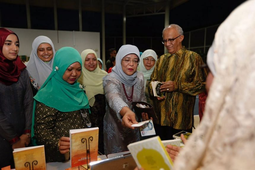 Club Heal's chief patron, President Halimah Yacob buys a book on auction at the charity's fifth anniversary dinner held at Keat Hong Community Club on Jan 18.