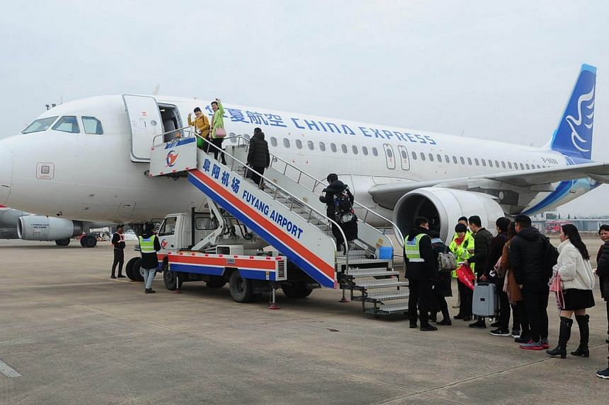 Passengers board a flight bound for Chongqing at Fuyang Xiguan Airport in Anhui province on Jan 15, 2018.
