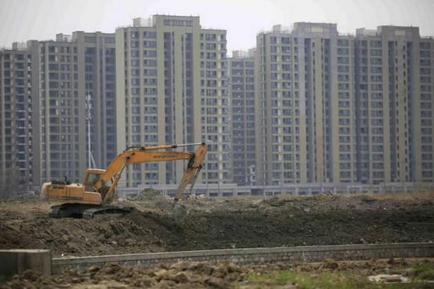 An excavator at a construction site of new residential buildings in Shanghai, China.