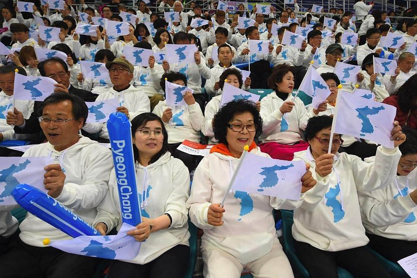 """South Korean fans waving """"unification flags"""" as they cheer for North Korean players during an IIHF women's world ice hockey championships match between South Korea and North Korea in Gangneung on April 6, 2017."""